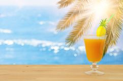 Image of tropical and exotic fruit coctail over wooden table infront of sea landscape background. stock photography