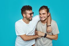 Portrait of two happy young hipster men embracing each other isolated over blue studio background stock photos