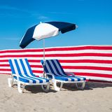 Two blue and white stripy deckchairs against clear blue sky. Image of two blue and white stripy deckchairs, Sunday 4 July 2016, De Haan, Belgium royalty free stock photography