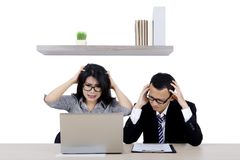Stressed business people working with a laptop. Image of two business people looks stressed while working with a computer laptop Royalty Free Stock Photos