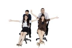 Business people with chair on studio. Image of two businesswomen sitting on the chair and pushed by their partner, isolated on white background Royalty Free Stock Photo