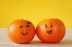 Image of two clementines with drawn smiley faces Stock Photography