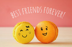 Image of two cute macaroons with drawn smiley faces Stock Photography