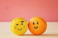 Image of two cute macaroons with drawn smiley faces. On wooden table. Best friend concept Stock Photography