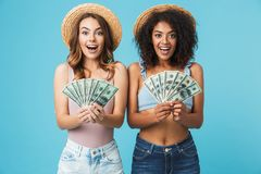 Image of two delighted girls 20s with different type of skin wearing straw hats rejoicing and holding fans of dollar banknotes, i. Image of two delighted girls royalty free stock photos