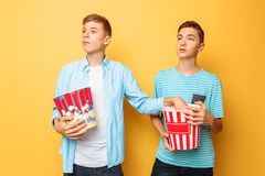 Image of two excited beautiful teenagers, guys watching an interesting movie and eating popcorn on a yellow background stock photography