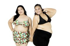 Happy fat women wearing swimwear. Image of two fat women looks happy while wearing swimwear, isolated on white background Stock Images