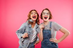 Funny women friends holding fake moustache and glasses. Image of two funny women friends standing isolated over pink background. Looking camera holding fake Royalty Free Stock Photos