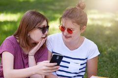 Image of two girls looking at smart phone and talking in park. Attractive females look thoughtful sitting on grass, speaks about royalty free stock images