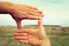 Image of two hands framing landscape composition Stock Photos