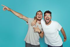 Portrait of two happy young men pointing fingers away isolated over light blue background. Friendship concept royalty free stock image