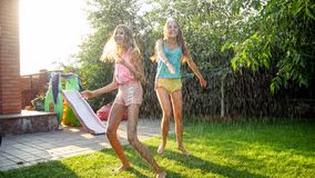 Photo of two happy laughing sisters in wet clothes dancing under water droplets from garden hose at garden. Family. Image of two happy laughing sisters in wet stock image