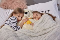 The image of two little sisters awakes in the morning stock image