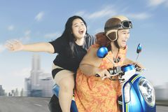 Obese women enjoying their journey with scooter. Image of two obese women enjoying their journey while driving a scooter with high speed along city road Royalty Free Stock Image