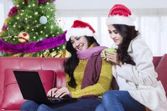 Two pretty girls using a laptop at home Royalty Free Stock Image