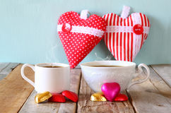 Image of two red heart shape chocolates and couple cups of coffee on wooden table. valentine's day celebration concept. Royalty Free Stock Photo