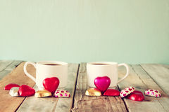 Image of two red heart shape chocolates and couple cups of coffee on wooden table. valentine's day celebration concept. Vintage filtered Stock Photos