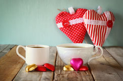 Image of two red heart shape chocolates and couple cups of coffee on wooden table. valentine's day celebration concept Royalty Free Stock Images