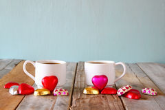 Image of two red heart shape chocolates and couple cups of coffee on wooden table. valentine's day celebration concept Royalty Free Stock Photos