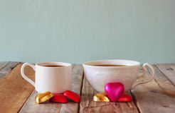 Image of two red heart shape chocolates and couple cups of coffee on wooden table. valentine's day celebration concept Stock Image
