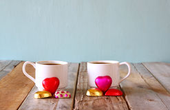 Image of two red heart shape chocolates and couple cups of coffee on wooden table. valentine's day celebration concept Stock Photo