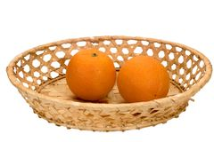 Two ripe oranges in a wicker plate Stock Photo