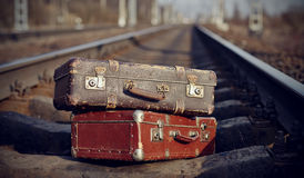 The image of two vintage suitcases on railway tracks. Royalty Free Stock Image