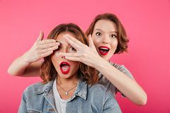 Two women friends covering eyes with hands. stock photos