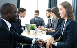 Image of two young business people interacting at meeting in office. Royalty Free Stock Photos
