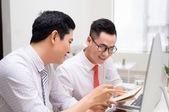 Image of two young businessmen interacting at meeting in office royalty free stock photography