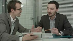 Image of two young businessmen using touchpad at stock footage