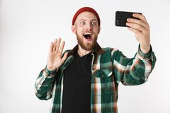Image of unshaved man wearing hat and plaid shirt taking selfie photo on cell phone, while standing isolated over white background. Image of unshaved man wearing royalty free stock photo
