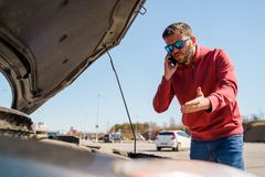 Image of upset man with phone in next to open hood of broken car in daytime. Outside stock photos