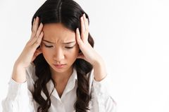 Image of upset or tired asian business woman 20s wearing office. Clothing sitting at table and grabbing head with hands isolated over white background stock images