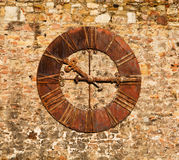 An image of a very old clock on a brick wall. An image of a very old metal clock with roman numerals showing 10:15am mounted on a brick wall Stock Photos