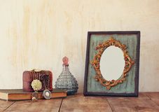 Image of victorian vintage antique classical frame, jewelry and perfume bottle. S on wooden table. filtered image Royalty Free Stock Photos