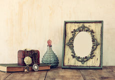 Image of victorian vintage antique classical frame, jewelry and perfume bottles on wooden table. filtered image.  Royalty Free Stock Photography