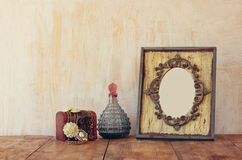 Image of victorian vintage antique classical frame, jewelry and perfume bottles on wooden table. filtered image.  Royalty Free Stock Image