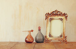 Image of victorian vintage antique classical frame and perfume bottles on wooden table. filtered image Royalty Free Stock Photography
