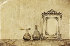 Image of victorian vintage antique classical frame and perfume bottles on wooden table. filtered image Stock Photos