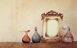 Image of victorian vintage antique classical frame and perfume bottles on wooden table. filtered image Royalty Free Stock Photo