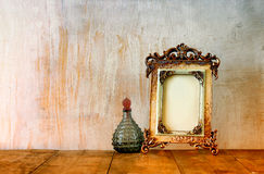 Image of victorian vintage antique classical frame and perfume bottles on wooden table. filtered image Stock Image
