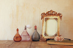 Image of victorian vintage antique classical frame and perfume bottles on wooden table. filtered image Stock Photography