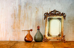 Image of victorian vintage antique classical frame and perfume bottles on wooden table. filtered image Stock Images