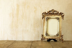 Image of victorian vintage antique classical frame on wooden table. filtered image Royalty Free Stock Image