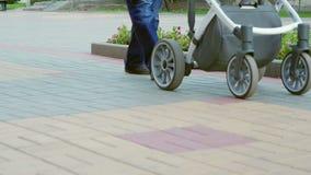 Image vidéo d'un homme méconnaissable avec un landau descendant la rue Le père heureux marche avec un enfant en parc banque de vidéos