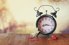 Image of vintage alarm clock next to autumn leaves on wooden table in front of abstract blurred background. retro filtered Stock Image