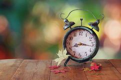 Image of vintage alarm clock next to autumn leaves on wooden table in front of abstract blurred background. retro filtered Stock Photo