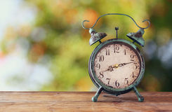Image of vintage alarm clock on wooden table in front of abstract blurred background. retro filtered. Stock Image
