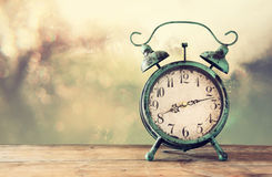 Image of vintage alarm clock on wooden table in front of abstract blurred background. retro filtered Stock Photo